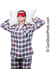 Sleeping woman on a pillow in plaid pajamas with a mask in...