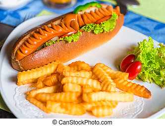 Fried potatoes and big tasty hot dog on a plate