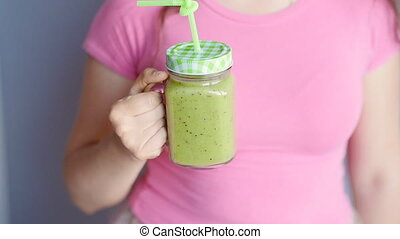 A happy woman holds a green smoothie in her hands