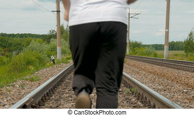 A man in sports uniforms runs on rails. He follows his...