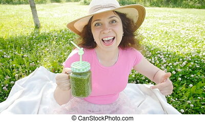 Young woman with green vegetable smoothies in the park -...