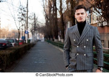 Man in fashion suit posing outside