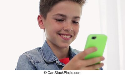 happy smiling boy with smartphone at home - children,...