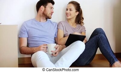 happy couple with tablet pc at new home - real estate,...