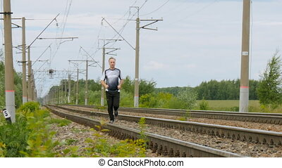 Man runs between rails on railroad tracks. Goes in for...