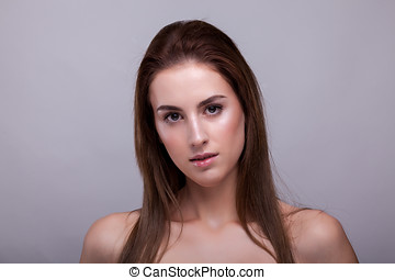 Portrait of beautiful woman with clean face on gray background