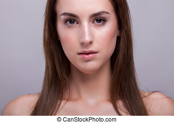 Beautiful fresh woman with no makeup in studio photo on gray...