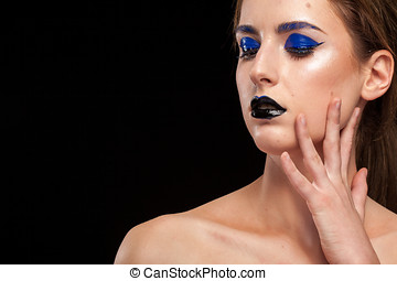 Model with extravagant fashion makeup posing in studio