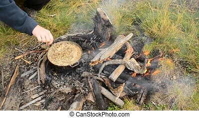 Hand of a woman stirring cereals cooking on bonfire in...