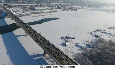 Quadcopter flying over a highway bridge across the Ob river....