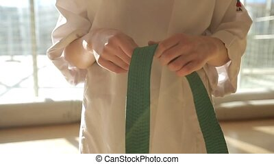 A young girl ties up a belt from kimono - A young girl ties...