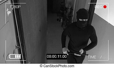 surveillance camera caught the robber in a mask with a crowbar