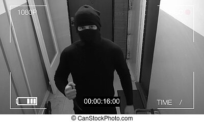 the masked robber burst through the door and threatened with a knife in CCTV camera