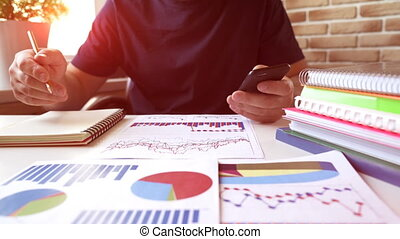 Businessman analyses stock charts, diagrams in financial report