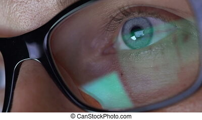 Closeup woman's eyes in glasses works on laptop at night -...