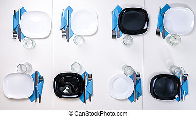 table setting for eight persons with white and black plates