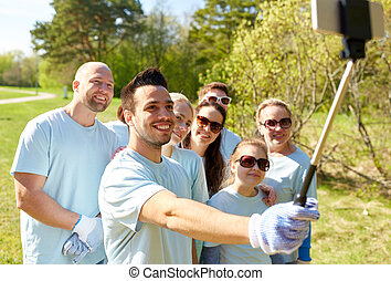 group of volunteers taking smartphone selfie - volunteering,...