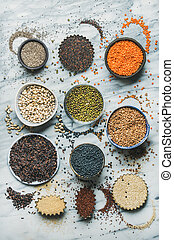 Variety of raw grains, beans, cereals over grey marble background