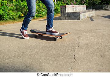 young skateboarder legs riding skateboard at skatepark -...
