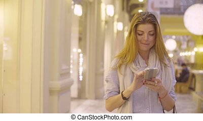Portrait of young woman walking with smartphone - Dolly shot...