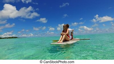 v07302 Maldives white sandy beach 2 people young couple man woman paddleboard rowing on sunny tropical paradise island with aqua blue sky sea water ocean 4k