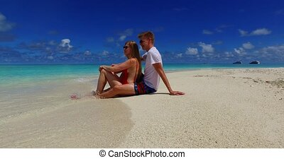 Maldives white sandy beach 2 people a young couple man woman sitting together on sunny tropical paradise island with aqua blue sky sea water ocean 4k