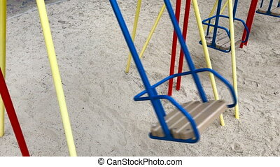 an empty swing moves outdoors
