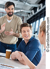 side view of smiling business people shaking hands on small office meeting