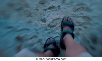 Man in sport sandals meets sunset on the sea and wiggles his...
