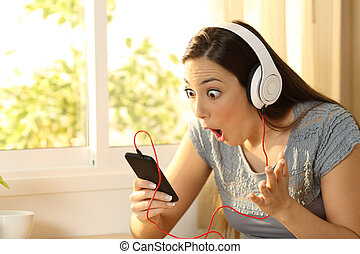 Amazed woman listening music finding offers on line in a...