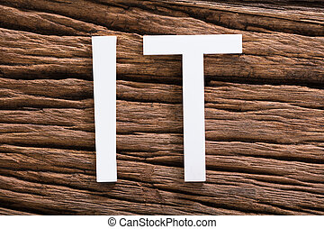 Elevated View Of White IT Text On Wooden Background