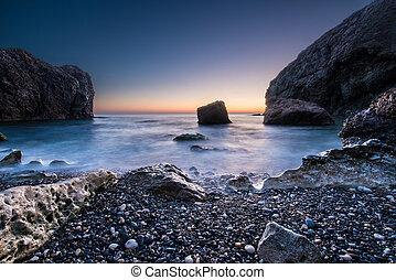 Scenic sunset on a rocky seashore