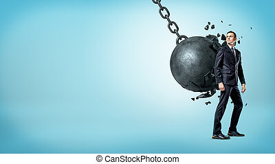 A businessman on blue background looking up over his shoulder white a wrecking ball crashes on his back.