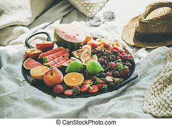 Tray full of fresh seasonal fruit over light blanket background