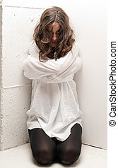 Young insane woman with straitjacket on knees looking at...
