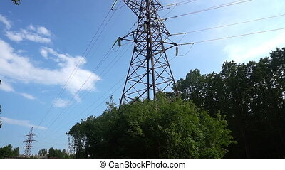Line of power transmission towers near the city, moving camera
