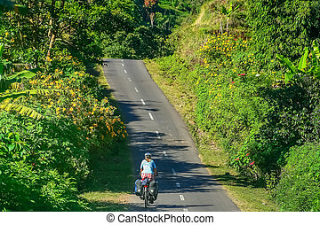 Cycling through Lombok - Female cyclist cycling through...