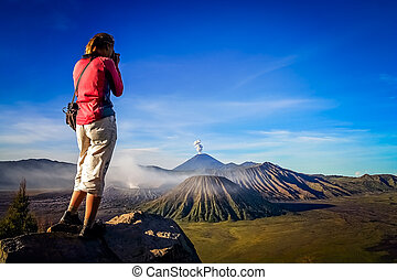 Photographing Gunung Bromo - Female trekker taking photos of...