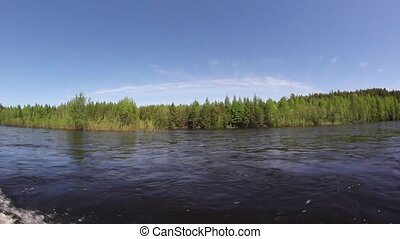 Forest from the side of a motor boat. Travel by river on a boat. Spring river.