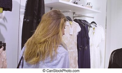 Young woman choosing dress in a clothing store 4K