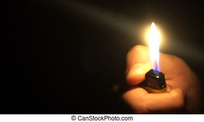 A close-up shot of a man igniting a lighter in the dark.