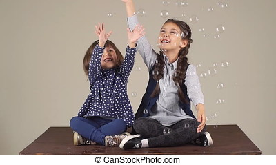 children play with soap bubbles and having fun. two little girlfriends laugh and smile. slow motion