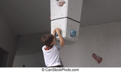 a boy climbs on a rock on the climbing wall. young athletic hung upside down on an artificial rock. slow motion