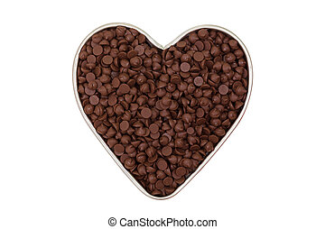 Sweetened chocolate chips in heart shaped tin bowl isolated...