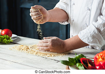 Closeup hand of chef baker in white uniform making pizza at...