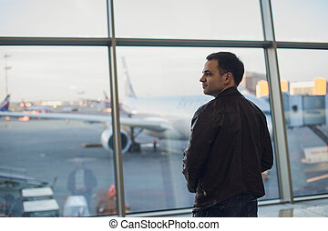 Young man is standing near window at the airport and watching plane before departure. Focus on his back