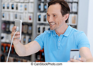 Side view on man taking self portrait with mockup phone -...