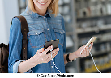 Close up of female customer holding two smartphones - They...