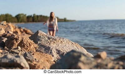 Young graceful woman walking barefoot on seaside