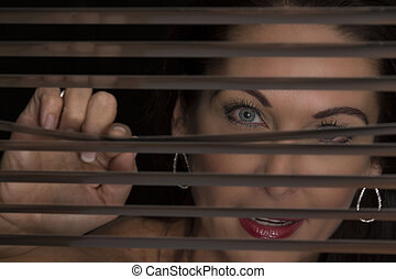 Portrait of a woman standing in darkness looking through blinds